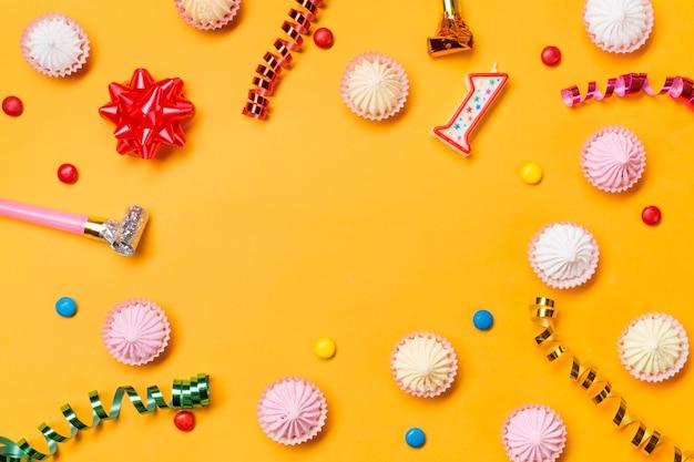 ストリーマリボンの弓。ナンバーワンのキャンドル。黄色の背景上の宝石