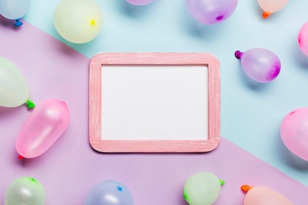 Белая пустая рамка украшена воздушными шарами на синем и розовом фоне