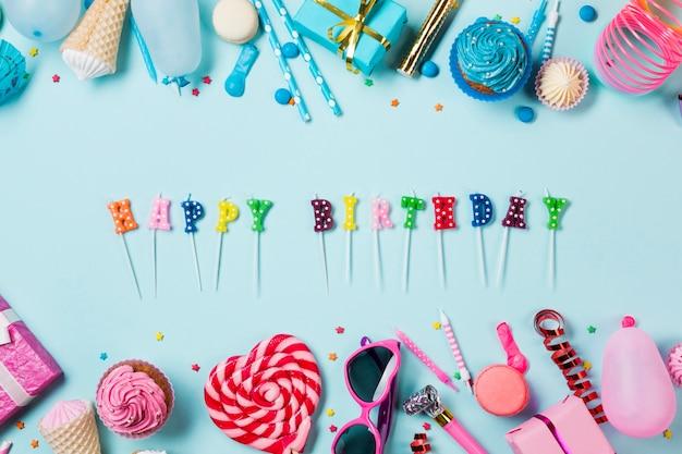 青い背景にカラフルな誕生日アイテムとハッピーバースデーキャンドル