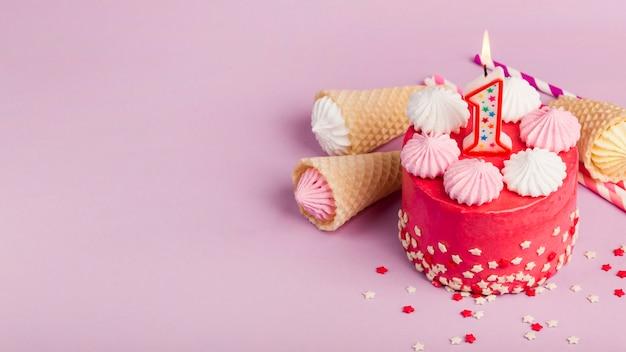 Вид сверху на декоративные красные пирожные с вафельными рожками и блюдцем на розовом фоне