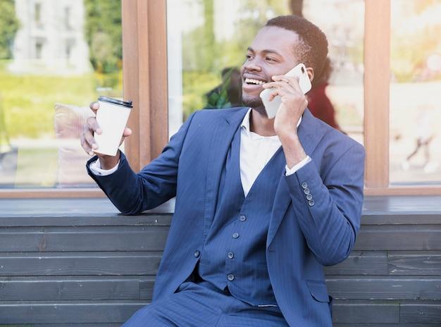 Портрет молодого африканского бизнесмена держа кофейную чашку на вынос говоря на мобильном телефоне