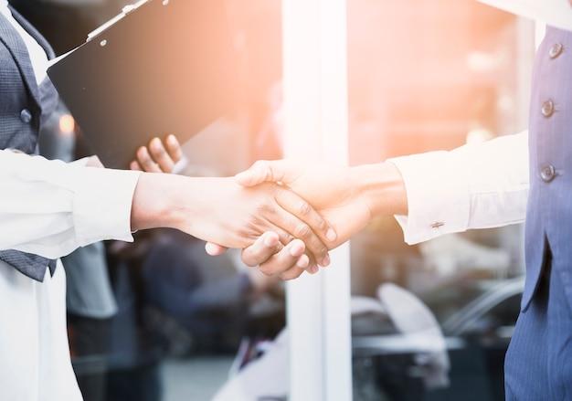 屋外で握手するビジネスマンおよびビジネスウーマンの手のクローズアップ