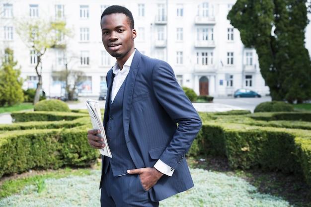 カメラ目線の新聞を保持している彼のポケットに手で自信を持って若いビジネスマン