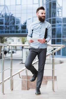 Молодой бизнесмен стоя вне корпоративного здания держа цифровую таблетку