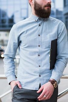 クリップボードを保持している彼のポケットに手を持つ若いビジネスマン