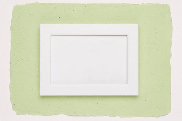 Белая пустая рамка на фоне зеленой бумаги