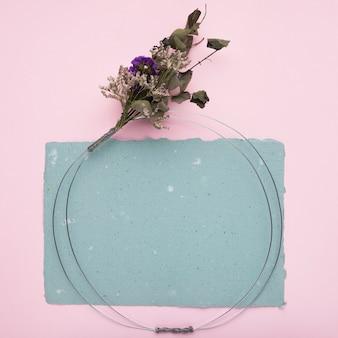 ピンクの背景の上の紙の上の花の花束と金属リング