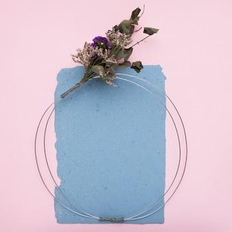 Пустая декоративная рамка с металлическим кабелем и букетом цветов на бумаге на розовом фоне