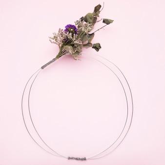 ピンクの背景のフレームの金属ワイヤーリングに縛ら花の花束