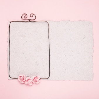 Прямоугольная проволочная рамка украшена розами на бумаге на розовом фоне