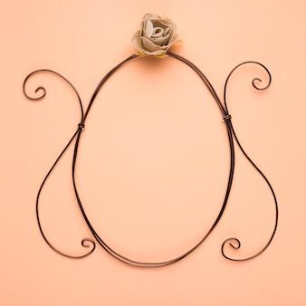 Роза над пустой овальной рамкой на персиковом фоне