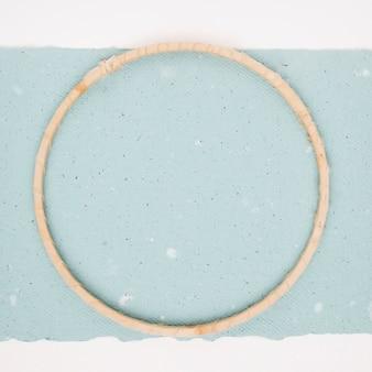 織り目加工の青い紙の上の木製の円形フレーム