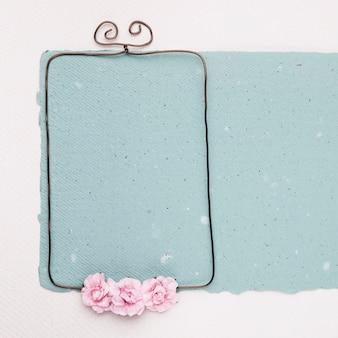 白い背景に青い紙の上の空の金属フレームにピンクのバラ