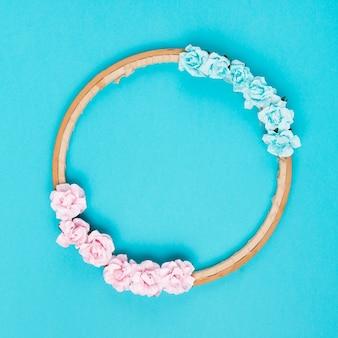 青い背景に木製の円形フレームにバラの装飾