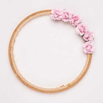 白い背景に円形の木製フレームに飾られたピンクのバラ
