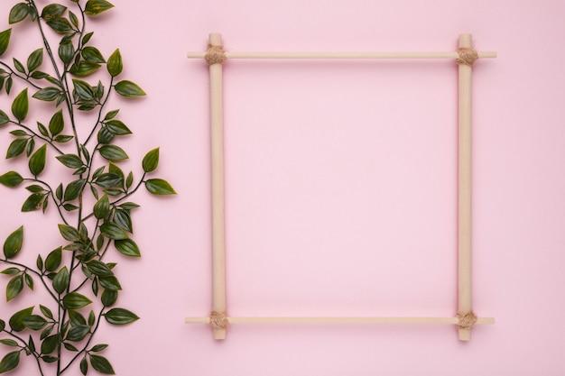 ピンクの背景に人工の緑の葉を持つ木製の正方形のフレーム