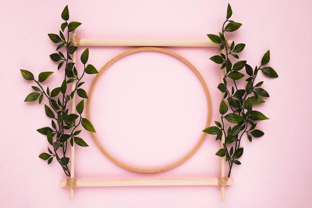 ピンクの壁に葉を持つ装飾的な木製の空のフレーム