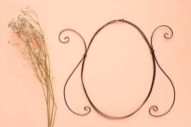 桃色の背景の空の楕円形フレームの近くの赤ちゃんの息の花