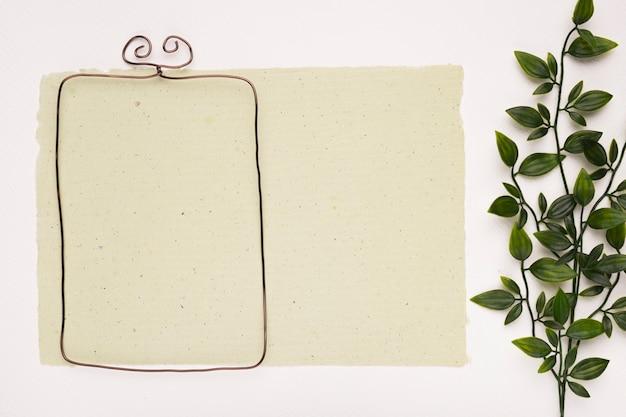 白い背景に人工の緑の葉の近くの紙の上の長方形の空のフレーム