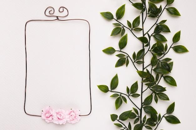 白の背景にピンクのバラで飾られた空のフレームの近くの緑の葉