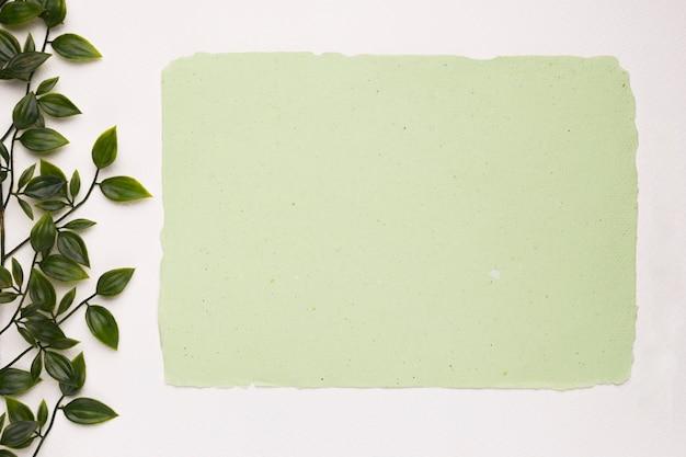 白い背景に分離された人工の葉の近くのミントグリーンペーパー