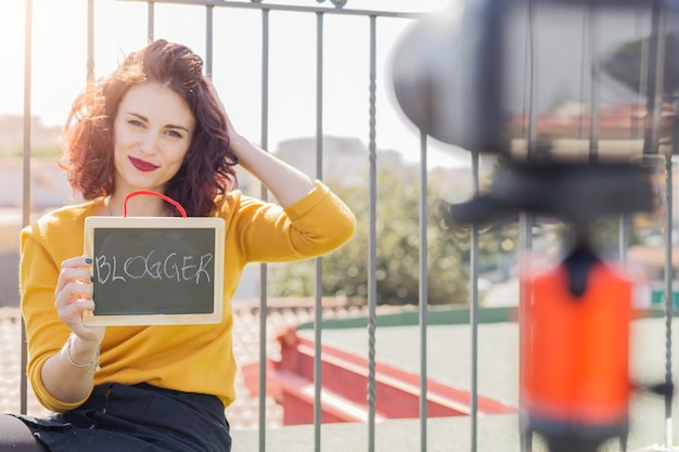 カメラに黒板を示すブルネットのブロガー