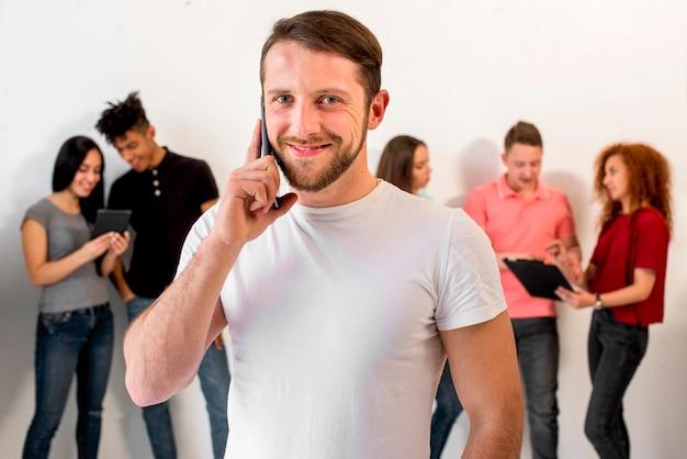 Красивый молодой человек разговаривает по мобильному телефону против своих друзей на фоне