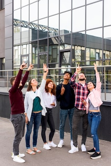 モダンな建物の前に上向きの通りに立っている若い友人のグループ