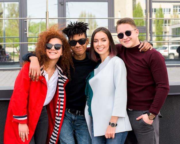 ガラス張りのモダンな建物に対して一緒に立っているファッショナブルな大学生のグループ