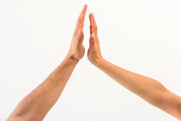 白い背景で隔離に対してハイファイブを与えるカップルの手のクローズアップ