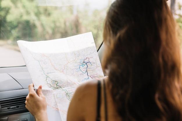 Женщина смотрит на карту в машине