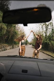 道路の真ん中に若いカップルの車からの眺め