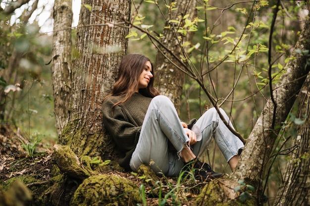 自然の中で座っている若い女性