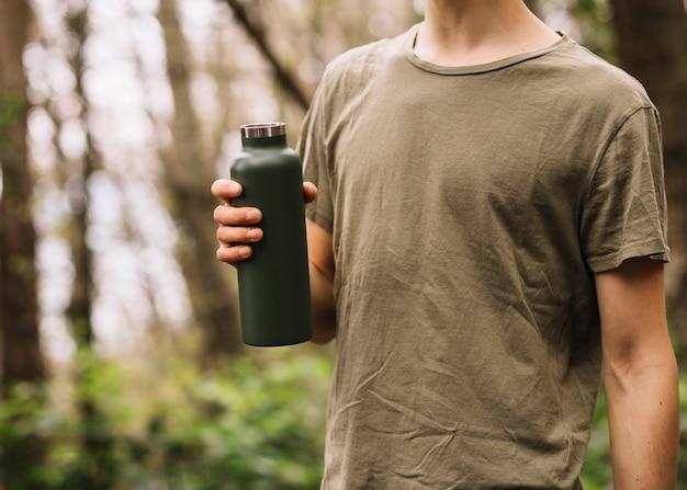 自然の中で水のボトルを保持している男