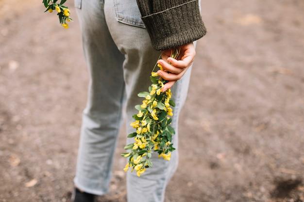 いくつかの野生の花を保持している若い女性