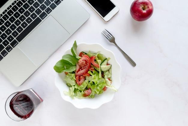 Повышенный вид безалкогольного напитка; тарелка салата; яблоко и вилка возле электронных устройств на белом фоне