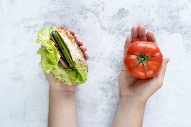 コンクリートの背景の上に手でトマトとハンバーガーを持っている人の手の立面図