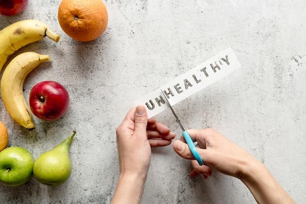 Человеческая рука режет нездоровое слово с ножницами возле здоровых фруктов