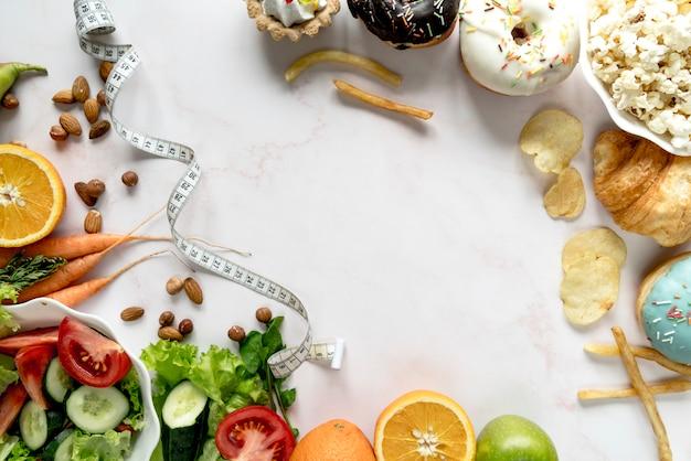 白い背景の上のフィット感と脂肪食品の概念と測定テープ