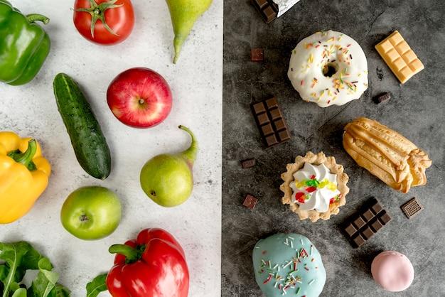 二重背景の上の健康的で不健康な食品の様々な