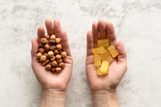 Конец-вверх руки человека показывая фундук и конфету над конкретной предпосылкой