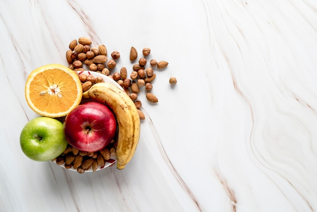 Половинка апельсина; яблоко; банан с миндалем и фундуком в миске