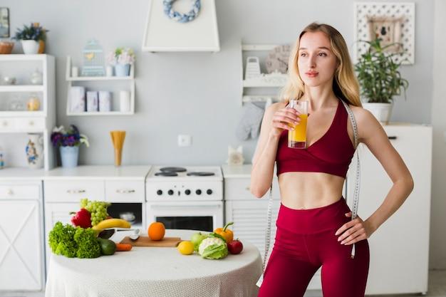 健康的なジュースとキッチンでスポーティな女性
