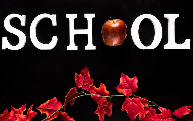黒の背景に赤いツタの枝の上の学校の言葉