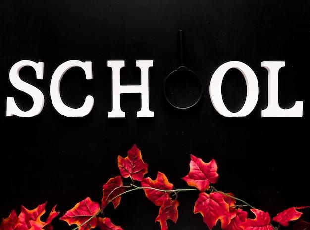 黒い背景に赤いツタの枝の上の白い学校単語