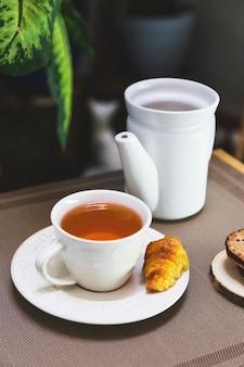 Чашка чая с чайником и элементами завтрака