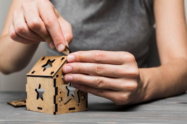 テーブルの上の手作りの家を作る女性のクローズアップ
