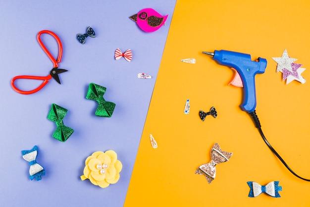 はさみと熱い接着剤銃二重背景の上の美しい様々なヘアクリップ