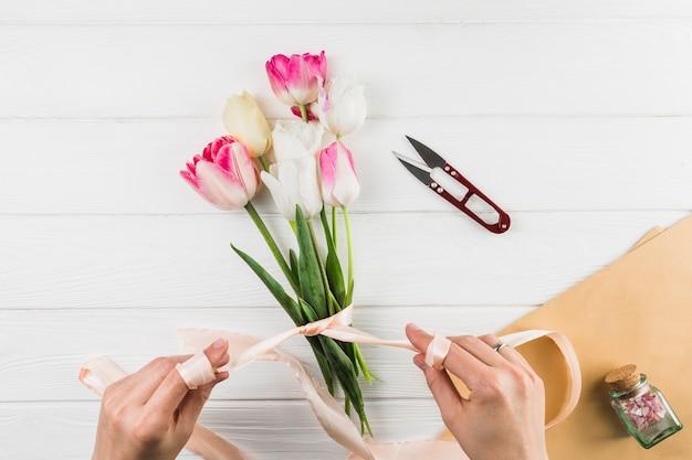 白い机の上のリボンとカッターを使用しながらチューリップの花の花束を作る女性の手のクローズアップ