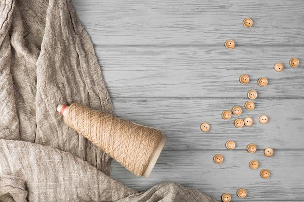 茶色のボタン。文字列スプールと木製の織り目加工の背景上の布